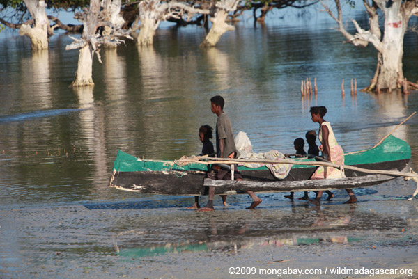 Malagasy family help their father carry his boat out to fish. Photo by: Rhett A. Butler.