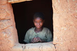 Girl looking out a window of a hut in a village in the Tsaranoro Valley [madagascar_6050]