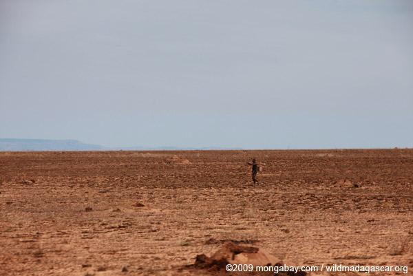 Man walking across a desolate wasteland